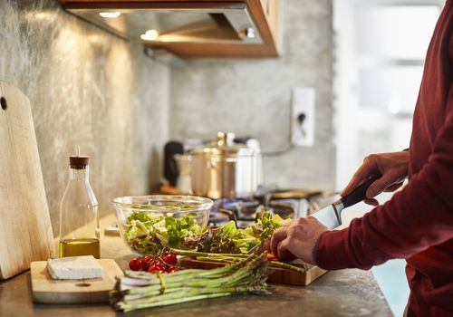 Man chopping salad and vegetables on countertop
