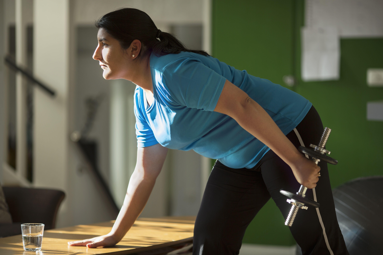 Mujer levantando pesas en casa