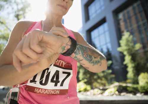 Tattooed female marathon runner checking smart watch in urban park