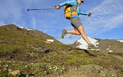 Female hiker jumping downhill