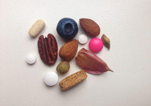 an assortment of pills, vitamins, fruits, nuts, garlic and cardamom
