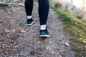woman walking in woods with tape on back of foot to prevent blisters