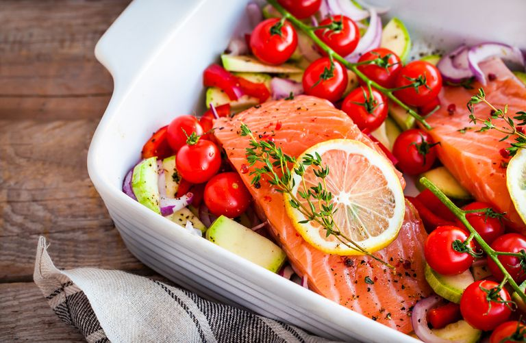A white casserole dish with cherry tomatoes, salmon, and vegetables