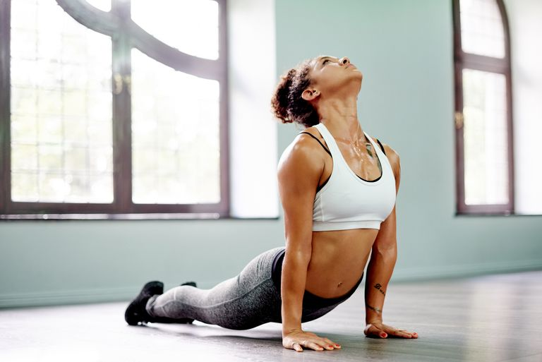 Woman sweating while doing upward facing dog pose