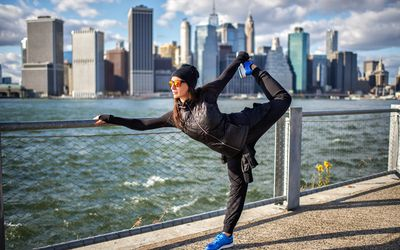 Female athlete stretching on the pier