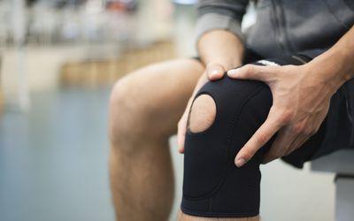man touching injured knee in brace