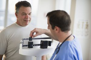 USA, New Jersey, Jersey City, Doctor assisting male patient on weighing scales in hospital
