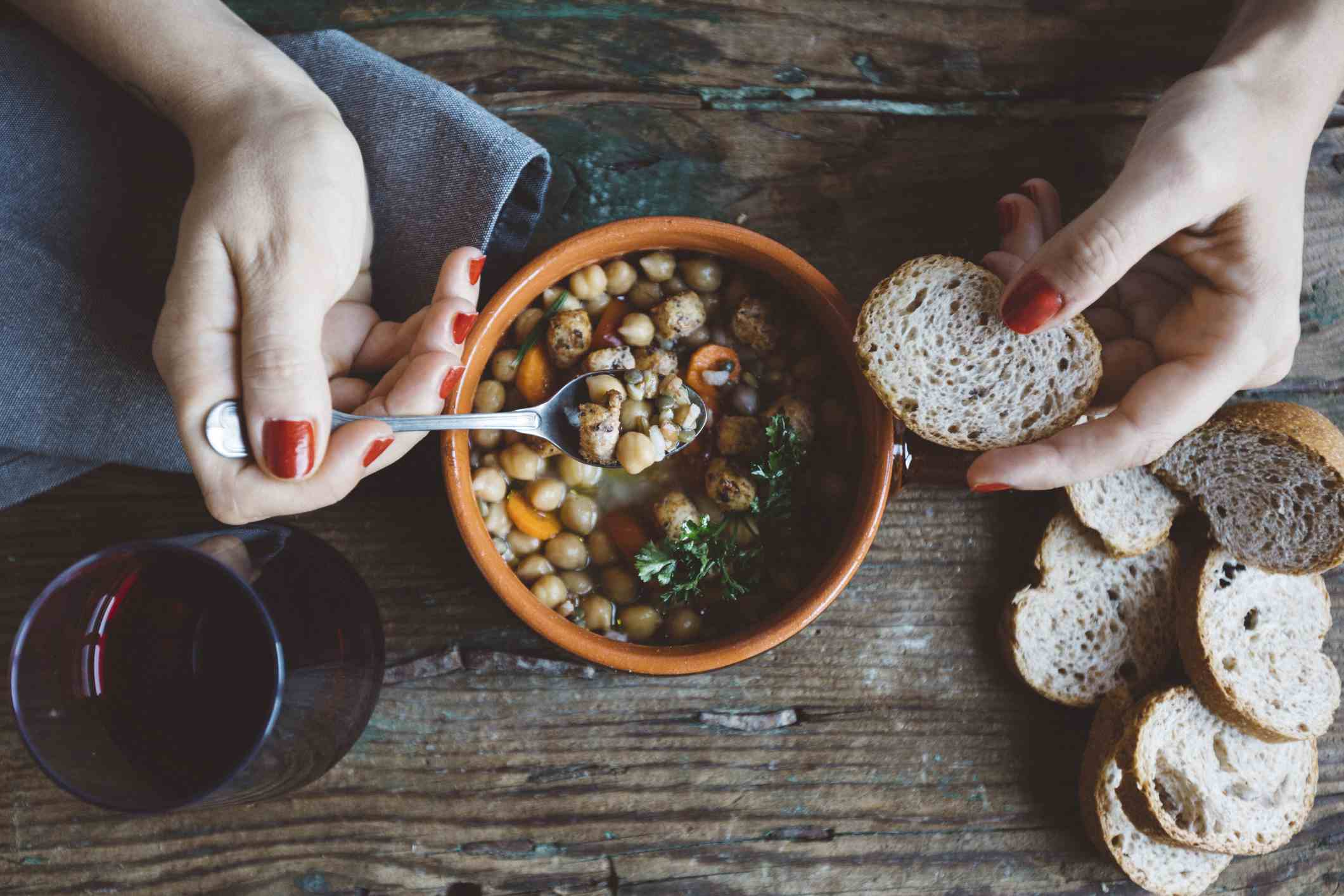 Woman eating Mediterranean soup with bread, close-up