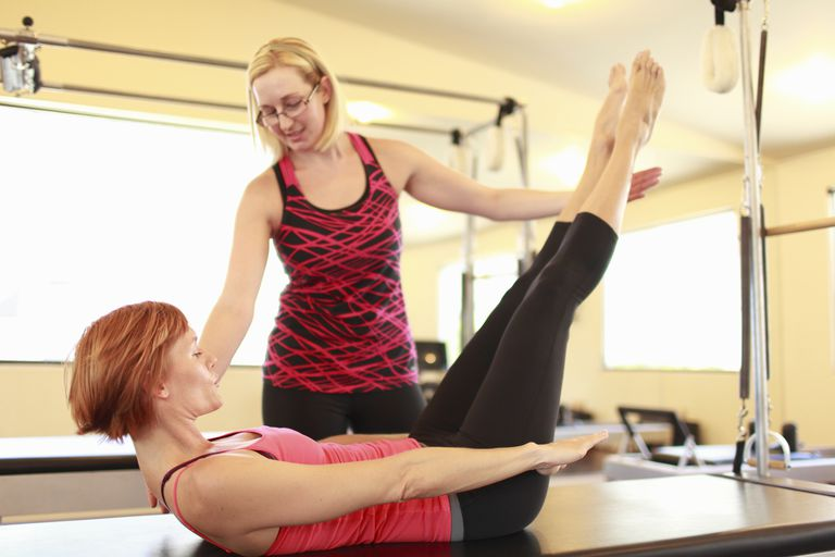 A Pilates instructor works with a student.