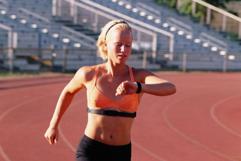 Female runner checking heart rate monitor