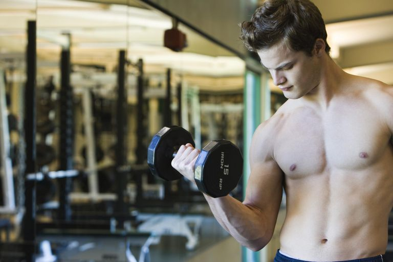 Barechested young man lifting dumbbell