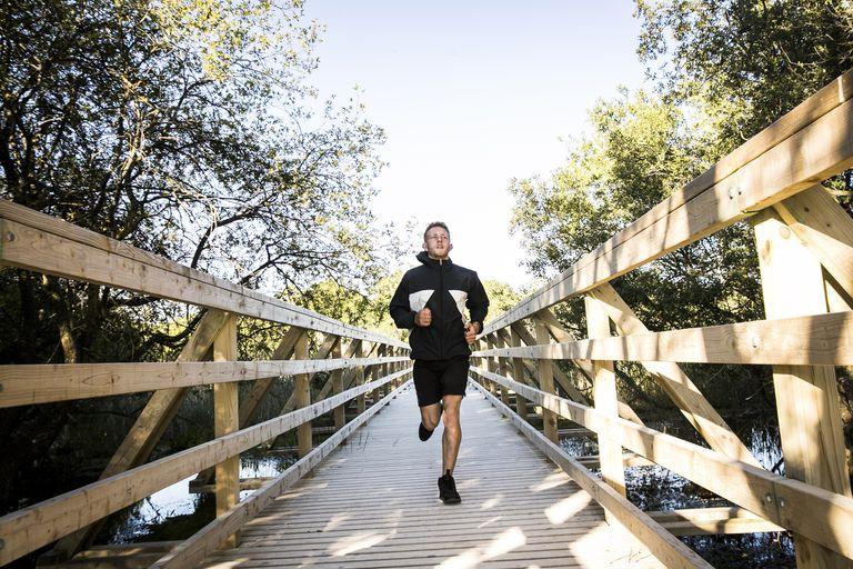 Young male runner running across rural footbridge