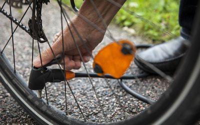 Cropped image of senior man repairing bicycle tire on street