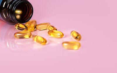 supplements spilling out of bottle onto pink background