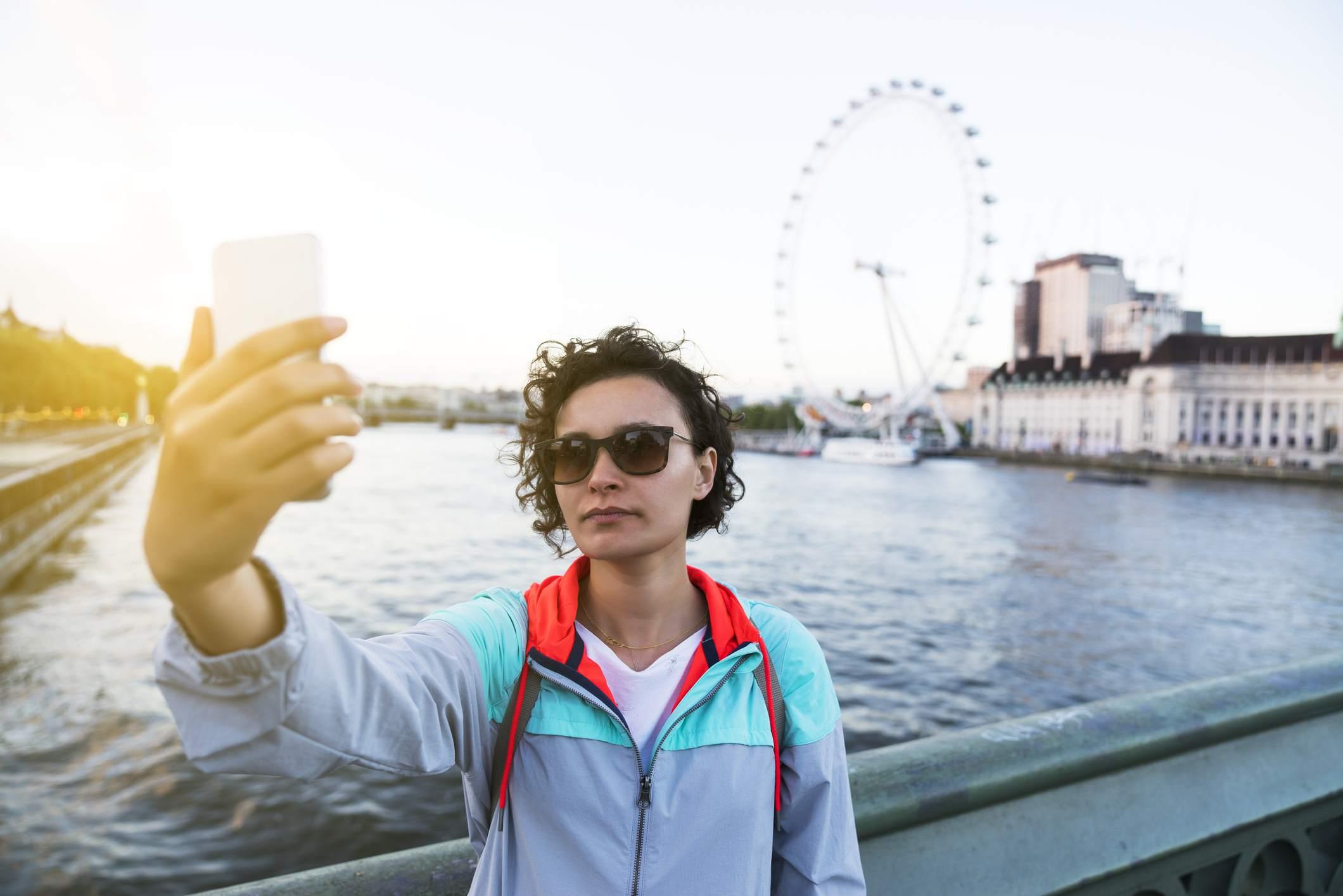 Mujer joven tomando selfie en Westminster Bridge, Londres