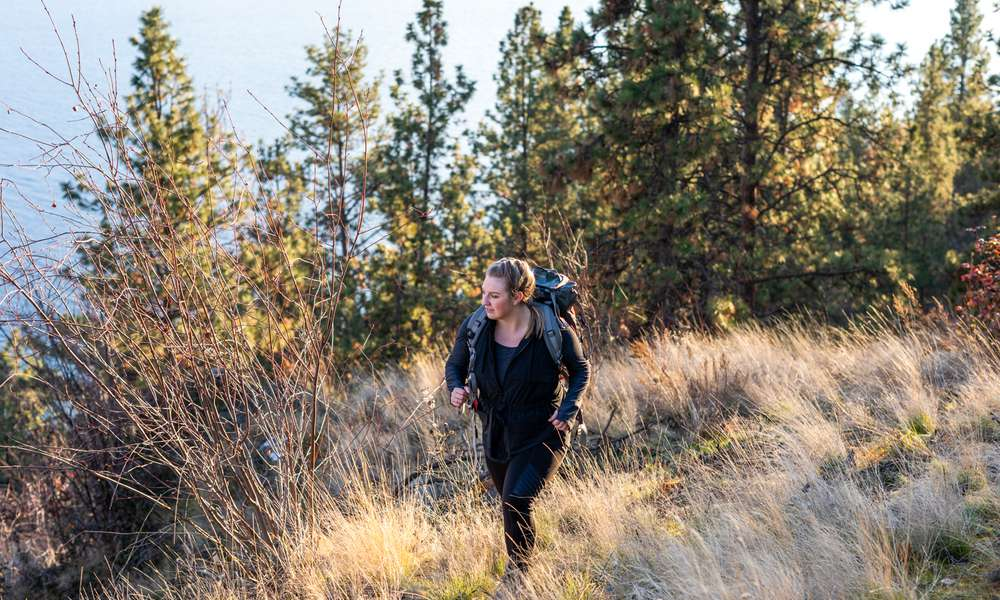 woman walking in the mountains with a hiking backpack