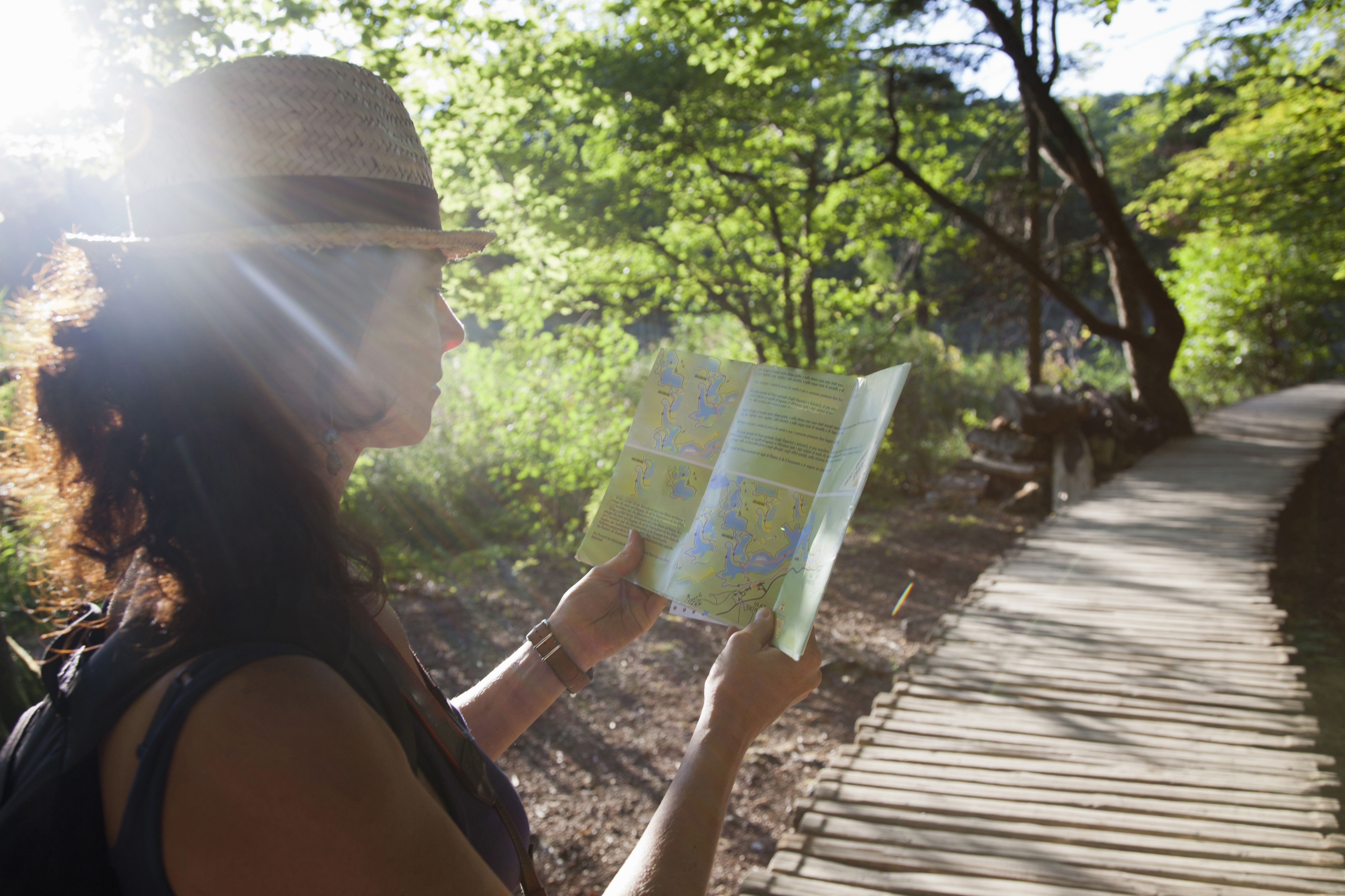 Woman reading map on wooden walkway