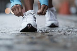 Mixed race runner tying shoelaces