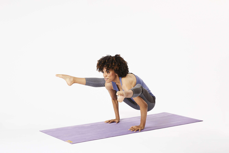 Woman on yoga mat doing firefly pose