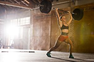 Female Athlete Lifting Barbell In A Warehouse Gym