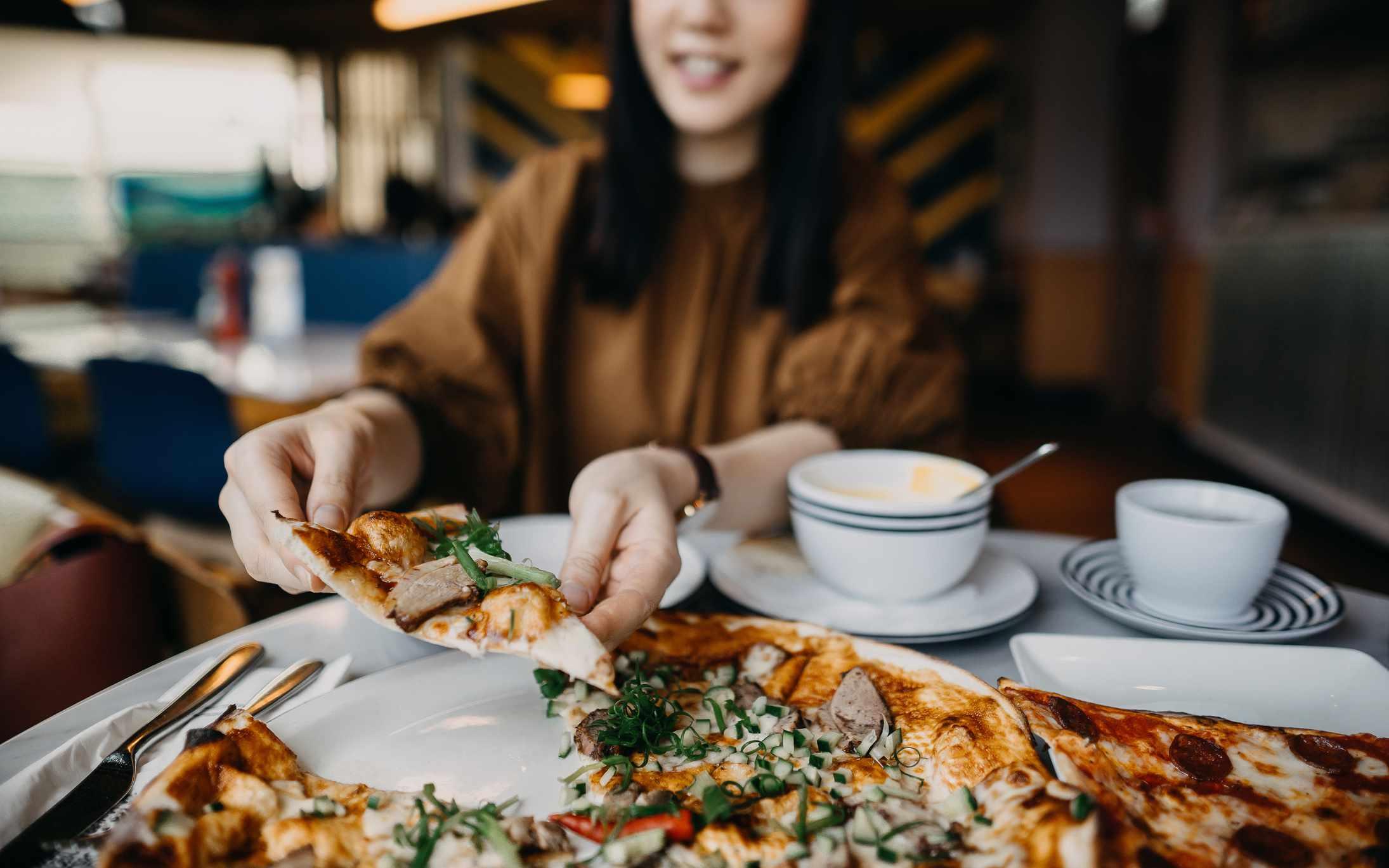Mujer alcanzando una porción de pizza.
