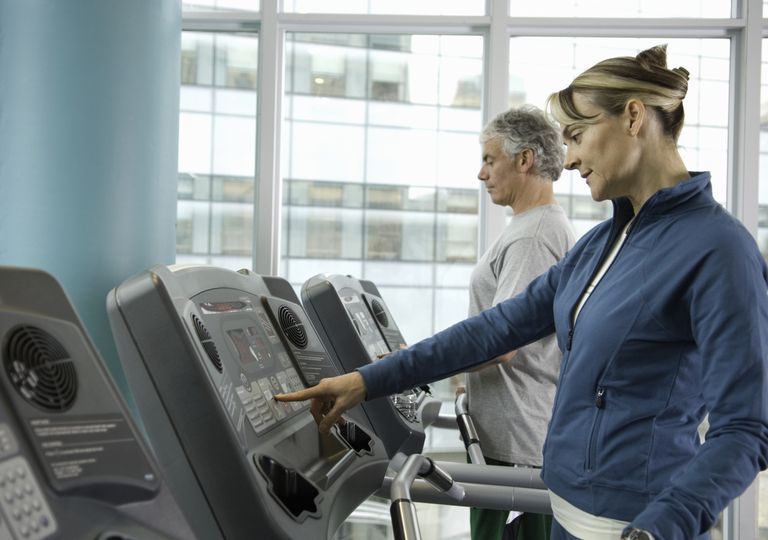 Mature woman looking at controls on treadmill in the gym