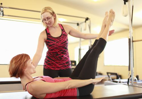 Un instructor de Pilates trabaja con un estudiante.