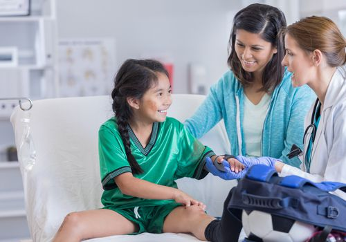Médico de urgencias habla con futbolista lesionado