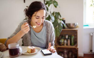 Woman eating looking at phone