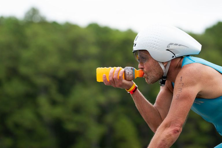 An athlete drinks Gatorade while cycling