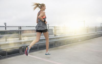 Young woman running, outdoors, rear view