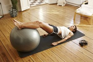 Young woman exercising at home with fitness ball