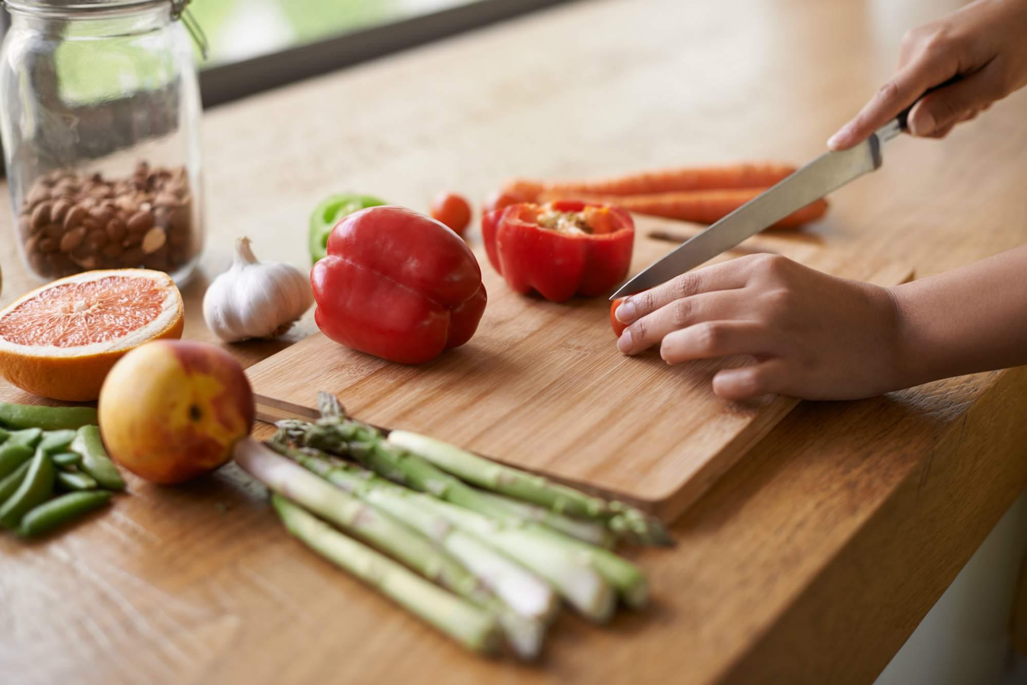 Woman cutting vegetables on a cutting board