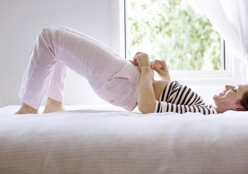 Woman Laying on Bed and Fastening on Pants