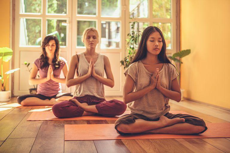 Three women meditating in integral yoga class