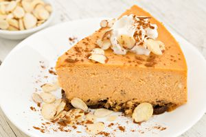 Pumpkin cheesecake on a plate garnished with sliced almonds, cinnamon, and whipped cream