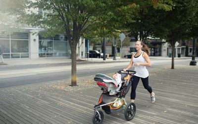 0c647632a84 Woman pushing baby stroller while running on floorboard