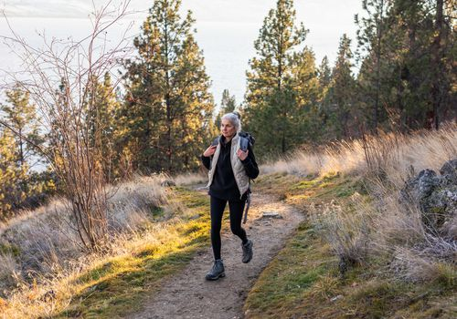 senior woman walking on mountain trail with hiking backpack