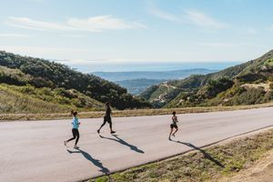 three runners jogging downhill on mountain road