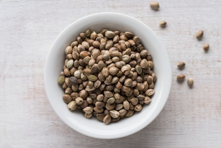 hemp seeds in a bowl with a few scattered on a white table