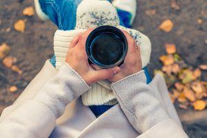 Woman holding coffee mug outdoors
