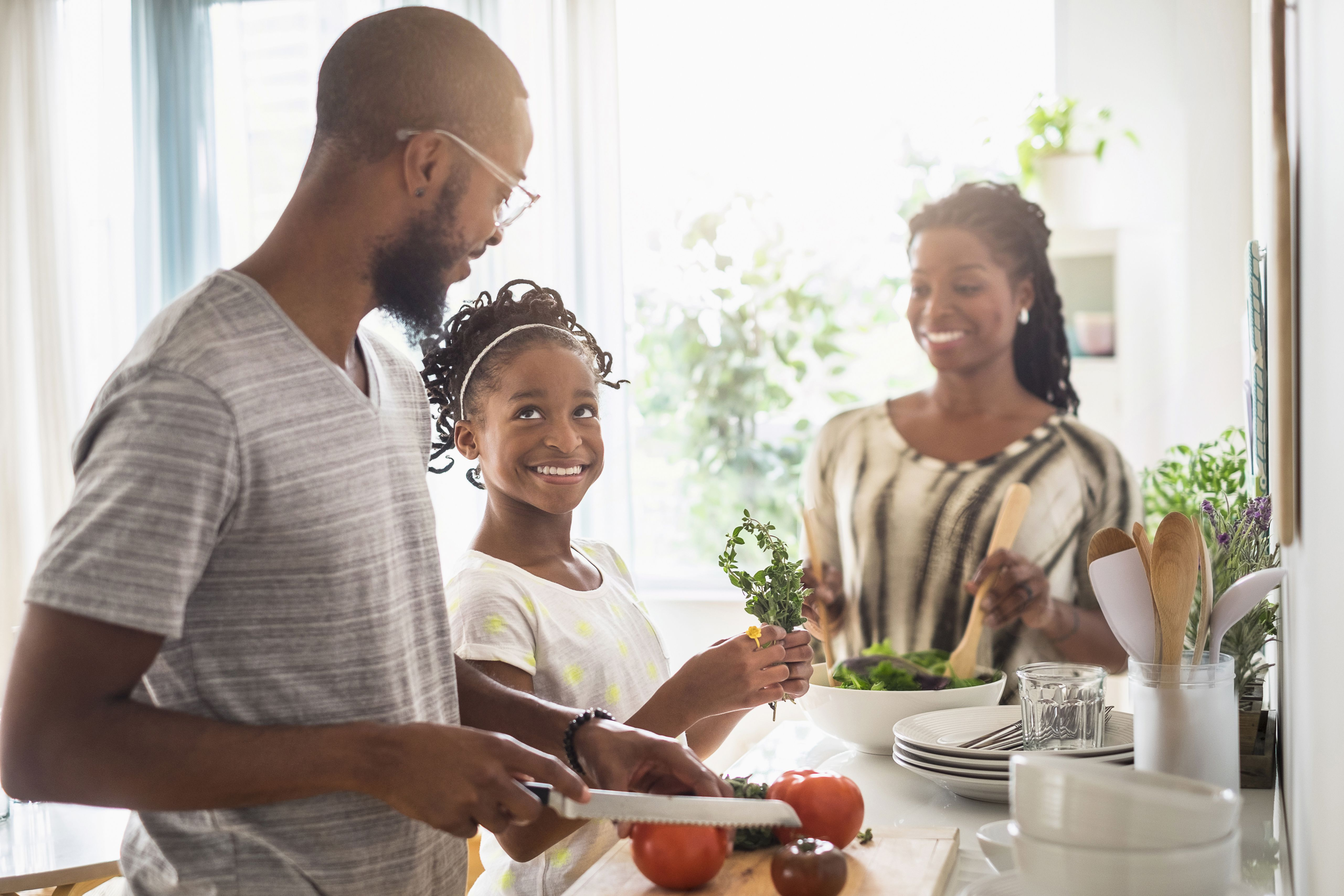 Familia negra cocinando en cocina