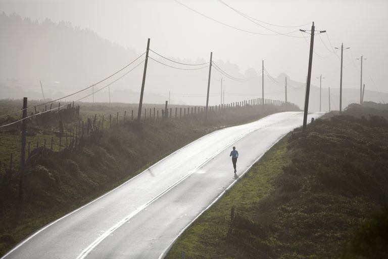A woman runs in morning fog on deserted road with telephone or electrical poles, northern California coast. (silhouette)
