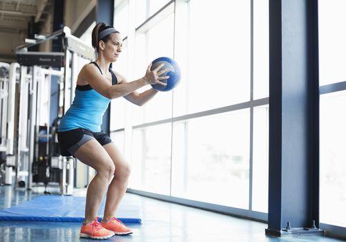 Mujer haciendo ejercicio con balón medicinal en el gimnasio