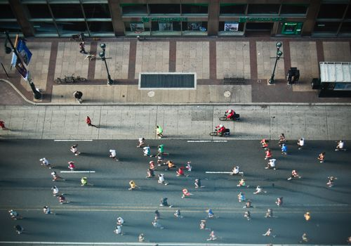 A group of marathoners running, photographed from an aerial view.