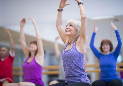 Personas mayores en una clase de ejercicio grupal sentados en pelotas de ejercicio y estirando los brazos sobre la cabeza