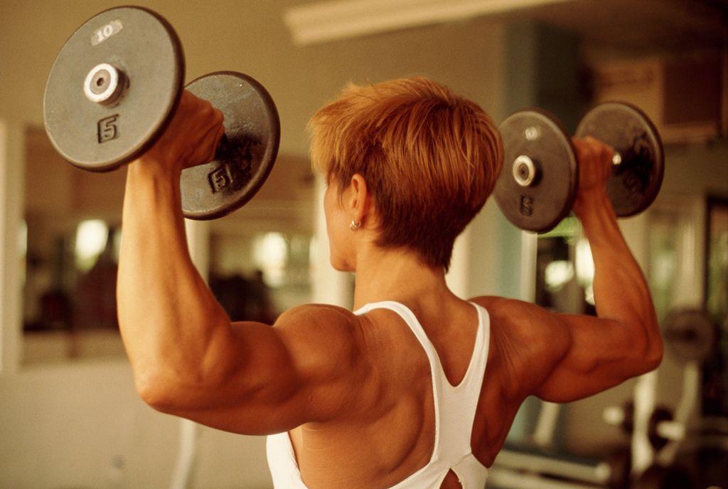 Mujer haciendo press de hombros, vista posterior