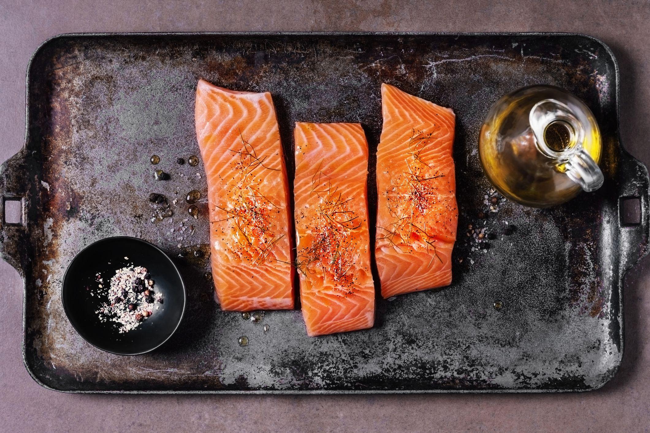 salmón en una bandeja para hornear con aceite de oliva y sal y pimienta