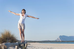 Woman walking on top of a log fence at beach