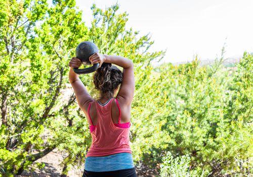 La parte posterior del joven en forma de mujer realizando pesas rusas halo